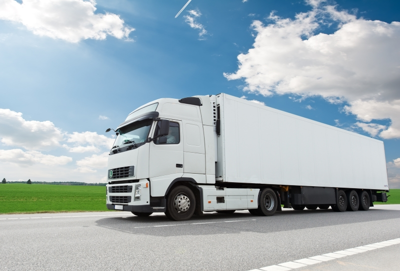 Single white lorry truck with trailer over blue sky on the road